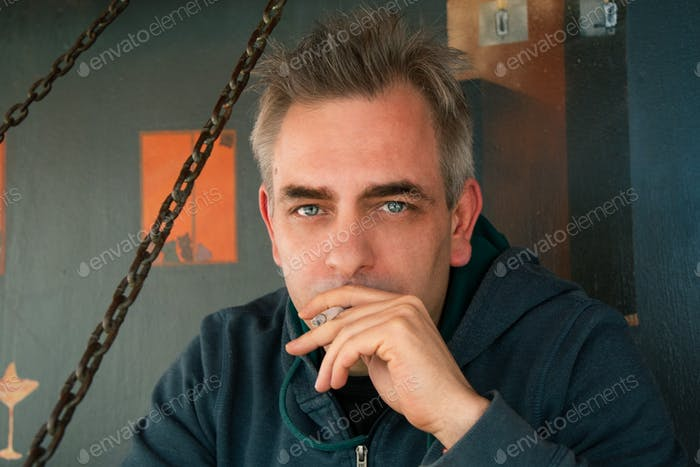 A man with blue eyes smokes a cigarette