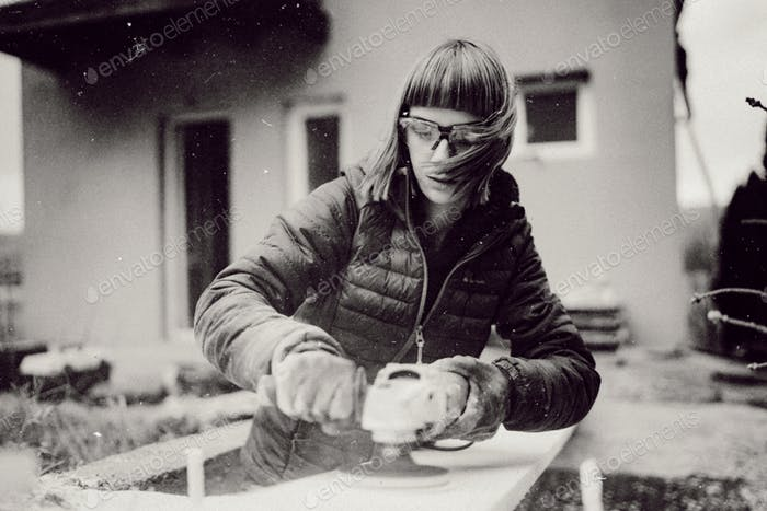 woman working on construction site with angle grider