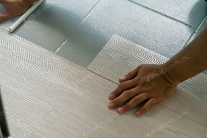 hand installing vinyl flooring