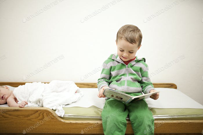 little boy in a green jacket and green pants sitting on an examination table in a doctors office wai