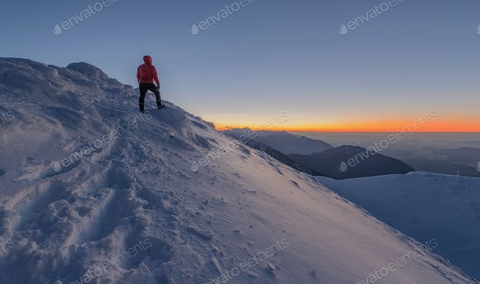 Male hiker waiting for the sunrise. Serenity in early morning in the mountains.