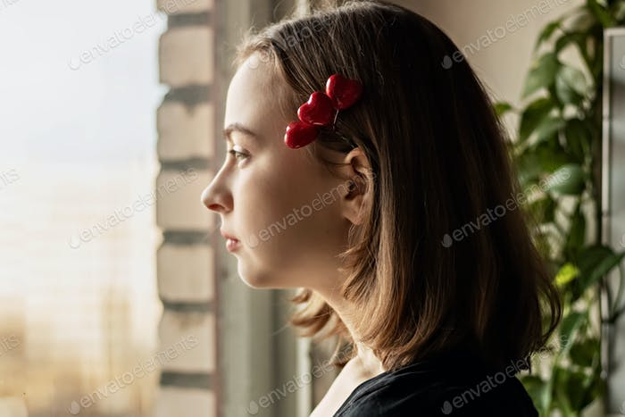 Portrait of a beautiful sad girl looking out the window with hope and expectation.