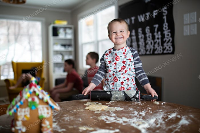 grinning toddler baking cookies