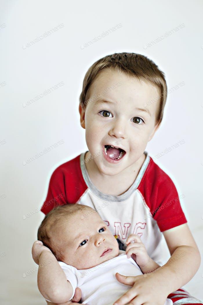 Junge hält neugeborenes Baby und Schauspiel überrascht