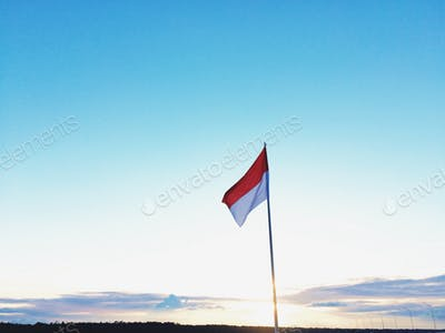 Indonesian national flag with sunset background.