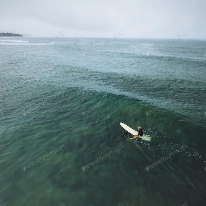 Woman sitting on surfboard