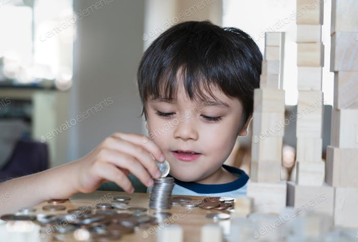 Selective focus happy kid stacking sterling pond coin with blurry foreground of coin on table. Child