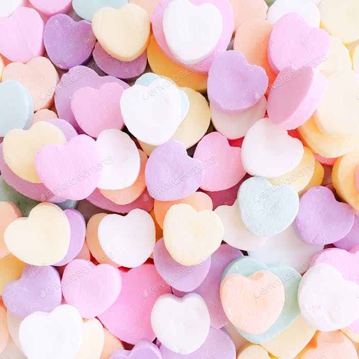 Full frame shot of stacked layers of pastel colored candy conversation hearts.