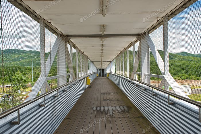 Diminishing perspective view of empty overpass with protective metal fence