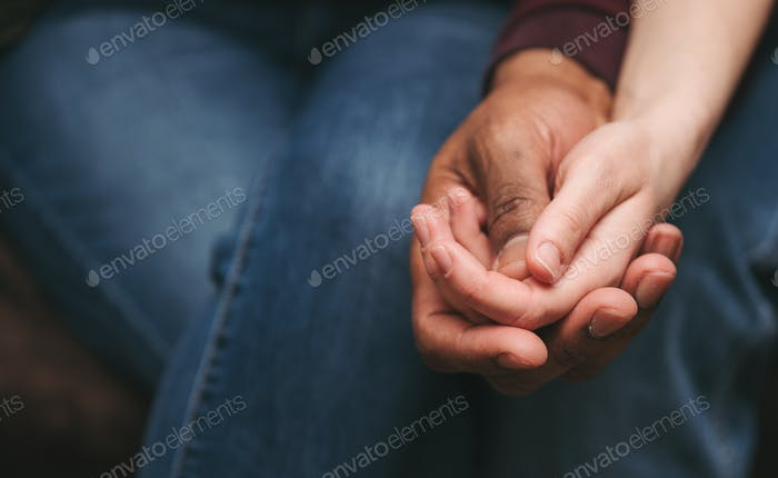 A close up of a mixed race heterosexual couple holding hands