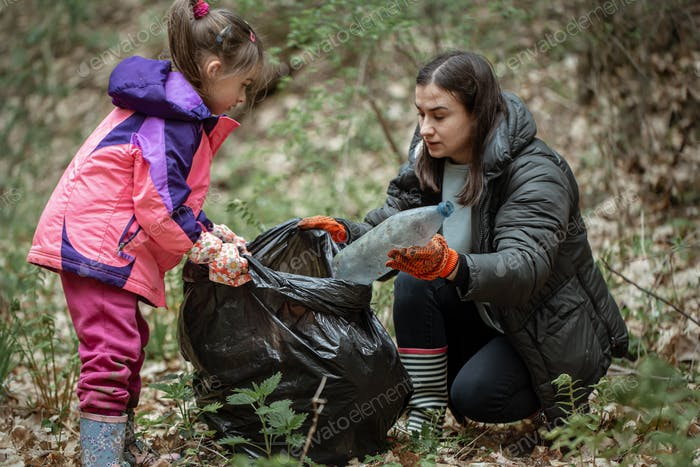 Mom and daughter are cleaning up garbage in the forest.