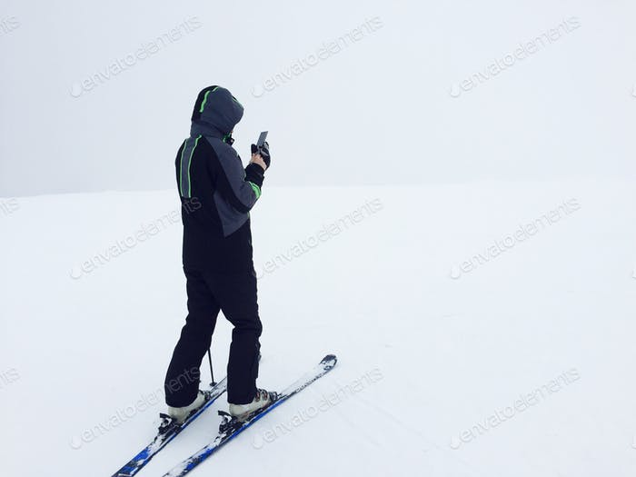 Skier in black ski costume with smartphone in his hand texting surrounded by fog and snow