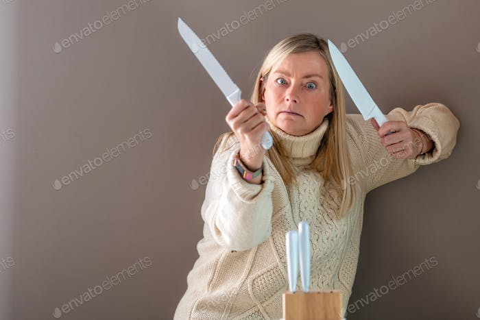 woman with two white knives in hand, in the foreground a set of kitchen knives on the table