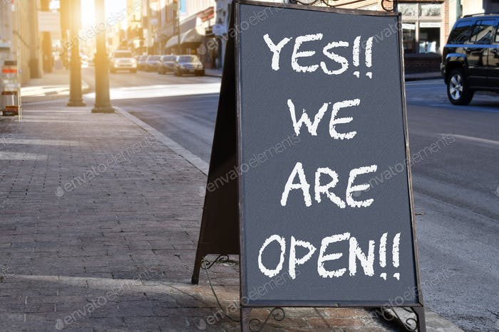 OPEN!!! Chalkboard sign on sidewalk proclaiming Yes We Are Open!!