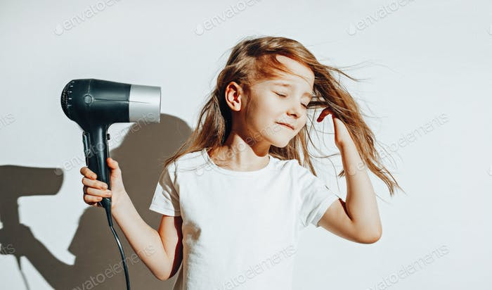 Girl dries her hair with a hair dryer