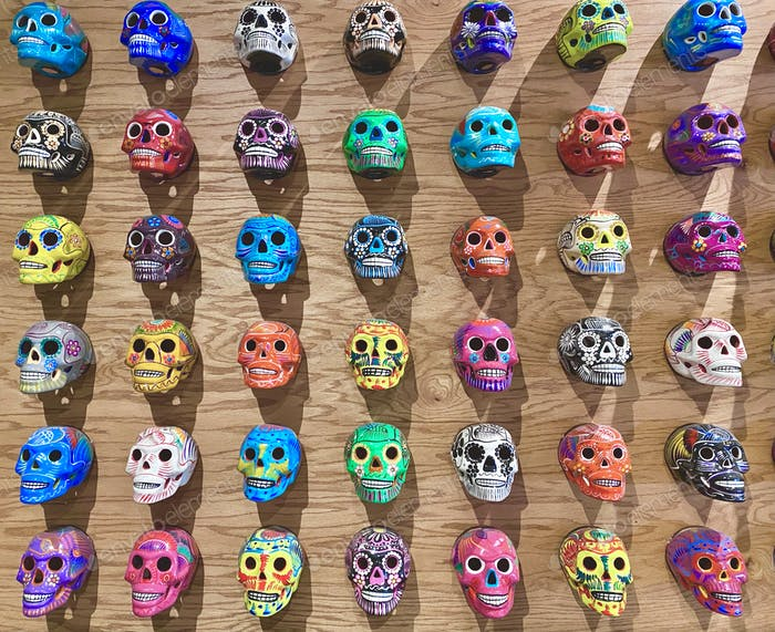 Bunter Flatlay-Hintergrund mit gemalten mexikanischen Schädeln für den Tag der Toten Dia de Los Muertos