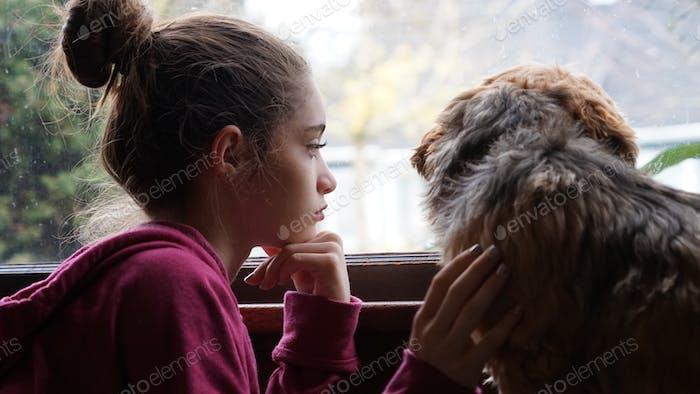 Pensando y viendo la lluvia por la ventana con el perro de su primo