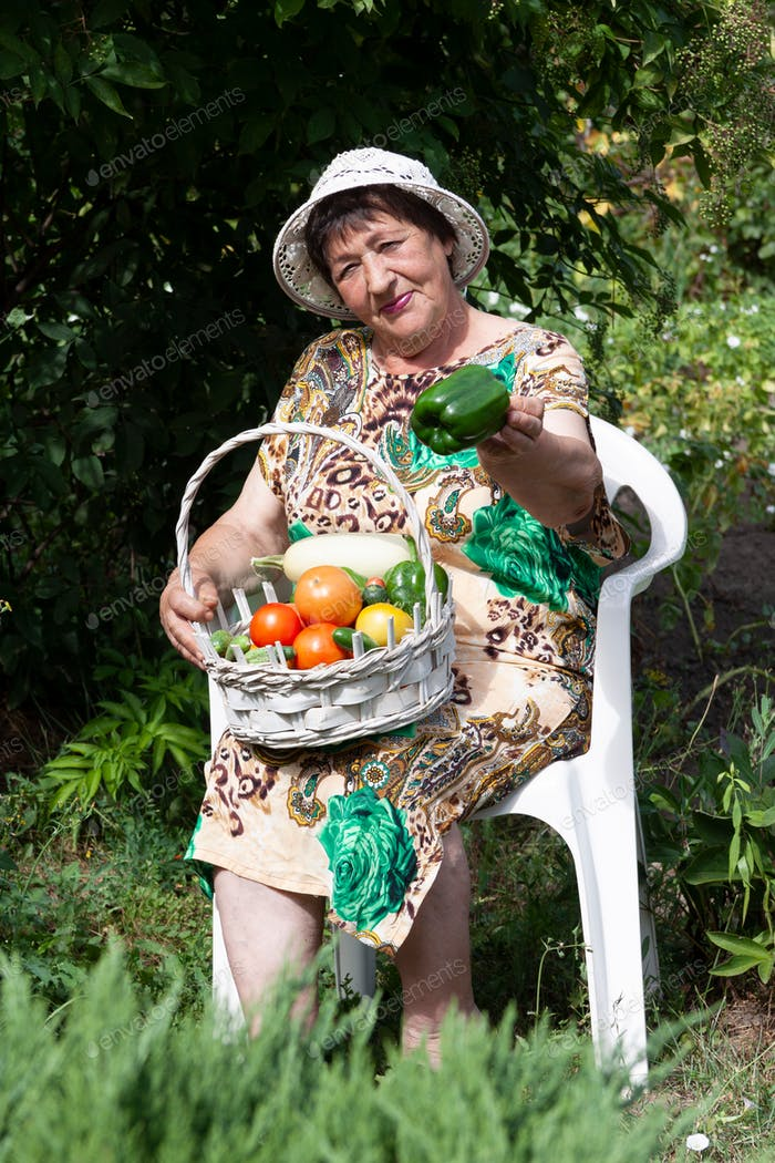 A pretty woman of 70-75 years old is sitting in the garden with a basket of vegetables.