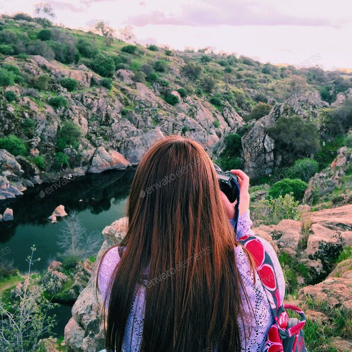 Young woman take photos of a landscape view.