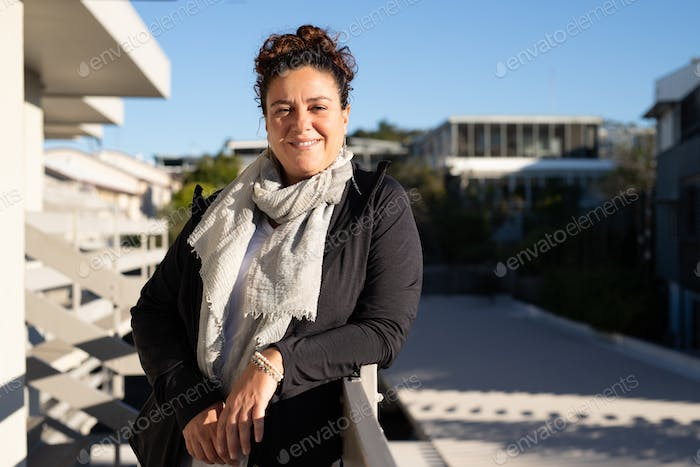 Latino Hispanic woman staying on the balcony on the sun, looking at camera and smiles