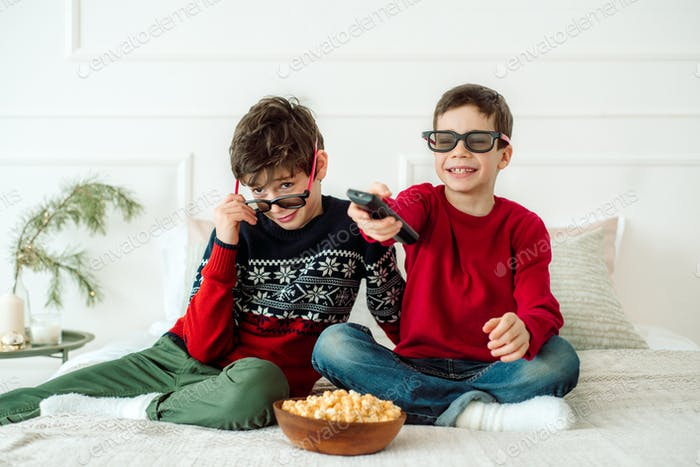 Cute children eating popcorn while watching TV at home in 3 d glasses.