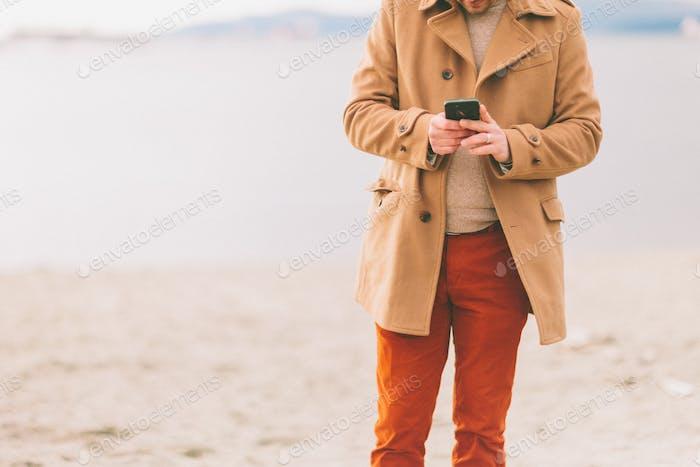 Хорошо одетый мужчина пишет на свой смартфон на пляже.