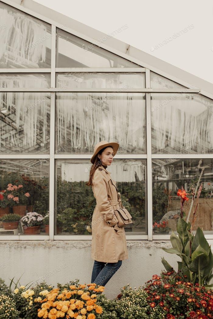 Girl is in autumn botanic garden. Beige tones, hat, cozy weather
