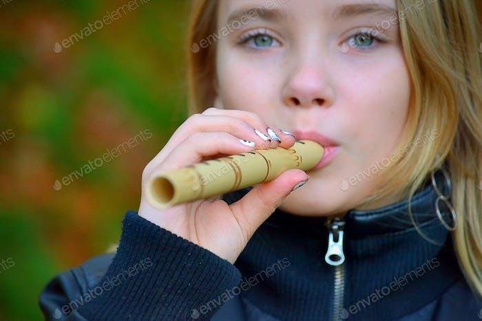Mädchen spielt auf einer Flöte