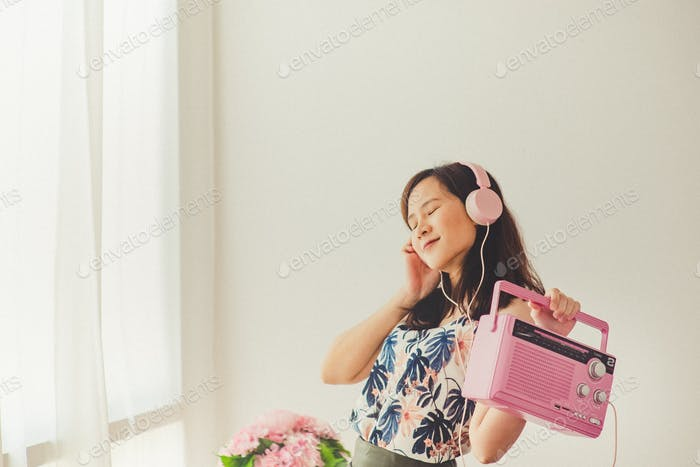 An asian woman listening to the pink radio trasistor. Dancing motion and wearing vintage cloth.