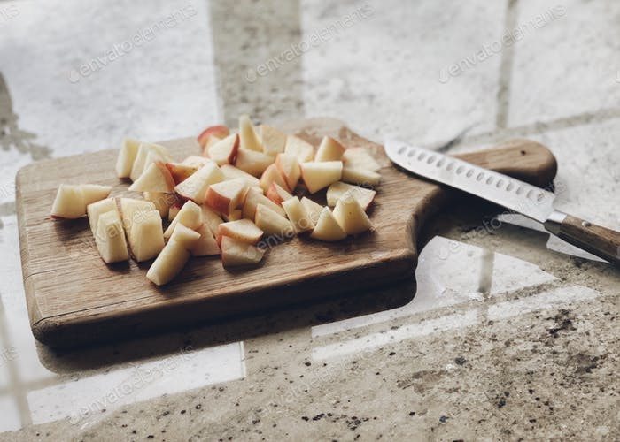 Chunks of fresh cut apples on a wooden cutting board atop a kitchen counter with background window