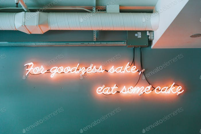 A neon sign that says 'for goodness sake, eat some cake' in an industrial room.