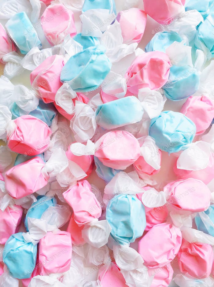Full frame shot of a messy pile of pink and blue wrapped candies.