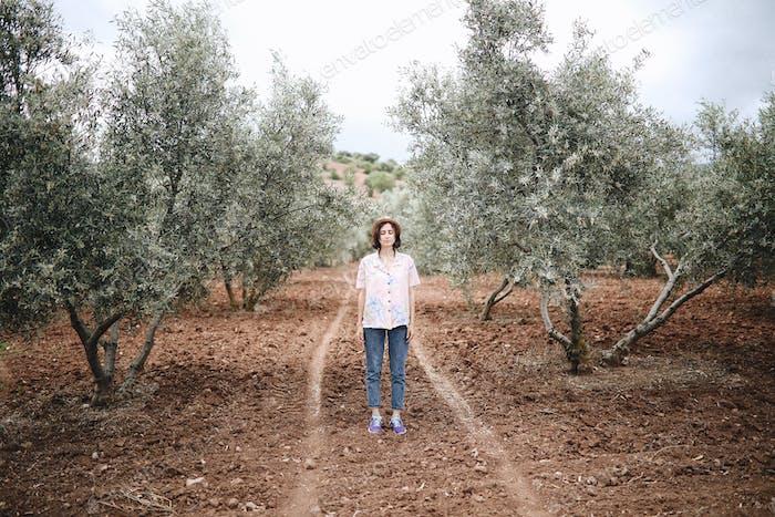 Tourist girl among olive trees