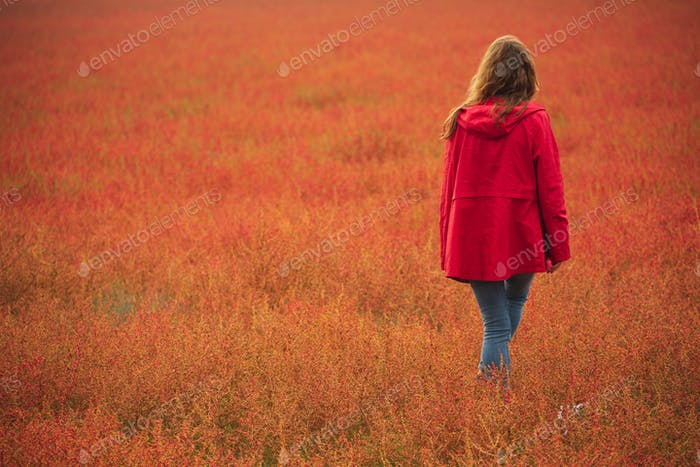 Young Woman  in a Red Windbreaker Walking  Back on Red Field. Autumn Season. Depressed Concept.