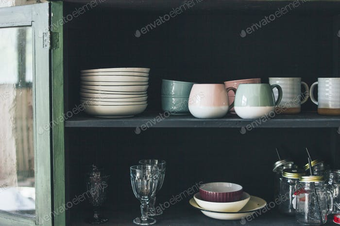 Vintage wooden green sideboard with dishes on rustic kitchen