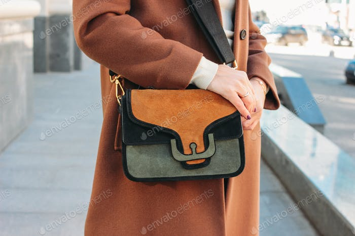 Fashionable stylish woman in a beige coat with a trendy suede bag