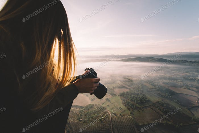 A young woman photographer taking pictures from a balloon