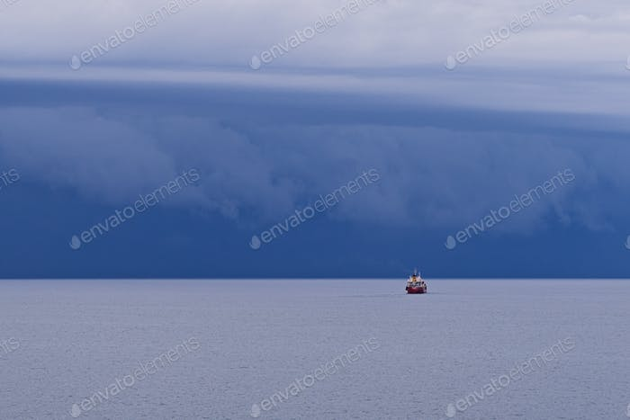 Amazing seascape with large thunderstorm clouds above sea surface with small red tugboat.