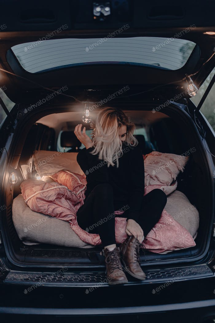 Woman travels by car. Sitting in a car trunk. Sleeping spot. Road trip. Lights. National forest.