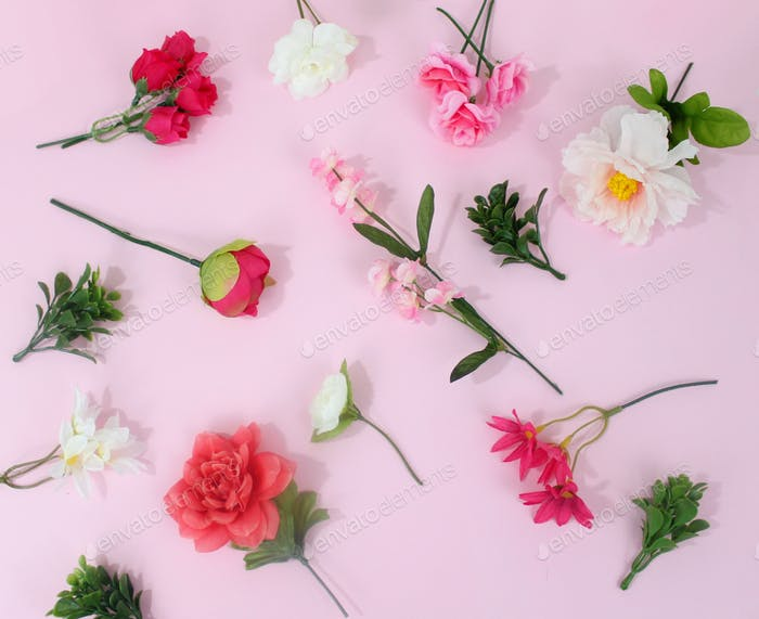 Faux flowers scattered across a pastel pink background.