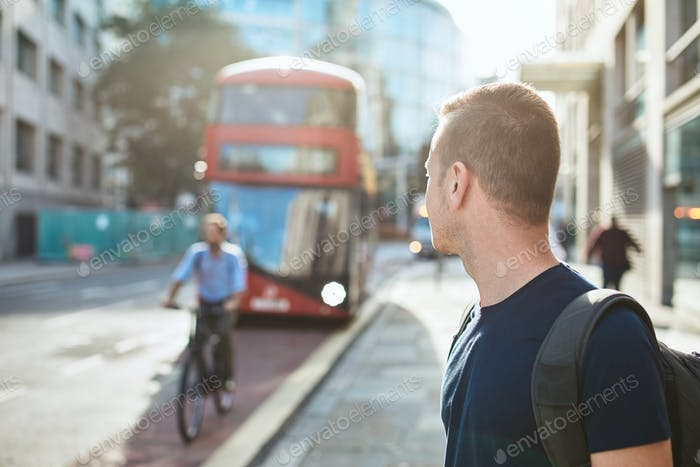 Young man waiting for bus of public transportation. City life in London, United Kingdom