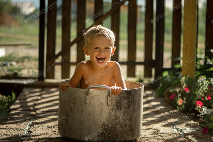 boy 4-5 years old in the summer in the village, the boy sits in an old huge saucepan. boy having fun