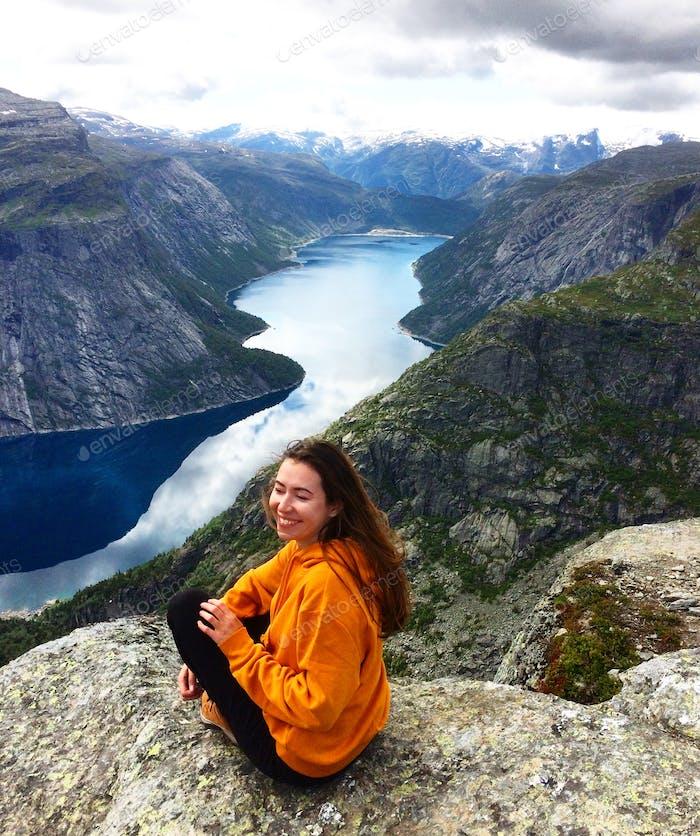 Una turista femenina, sonriente, con una sudadera amarilla brillante sentado en el borde de una roca, con una v