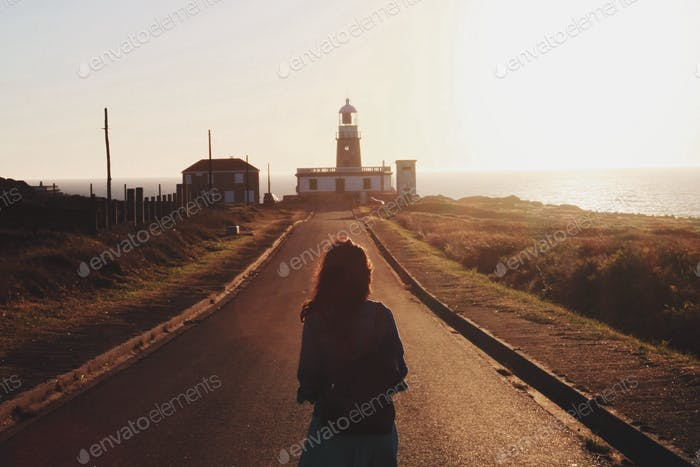 Woman walking towards a Lighthouse. Inspirational moment. Reflection and thought.