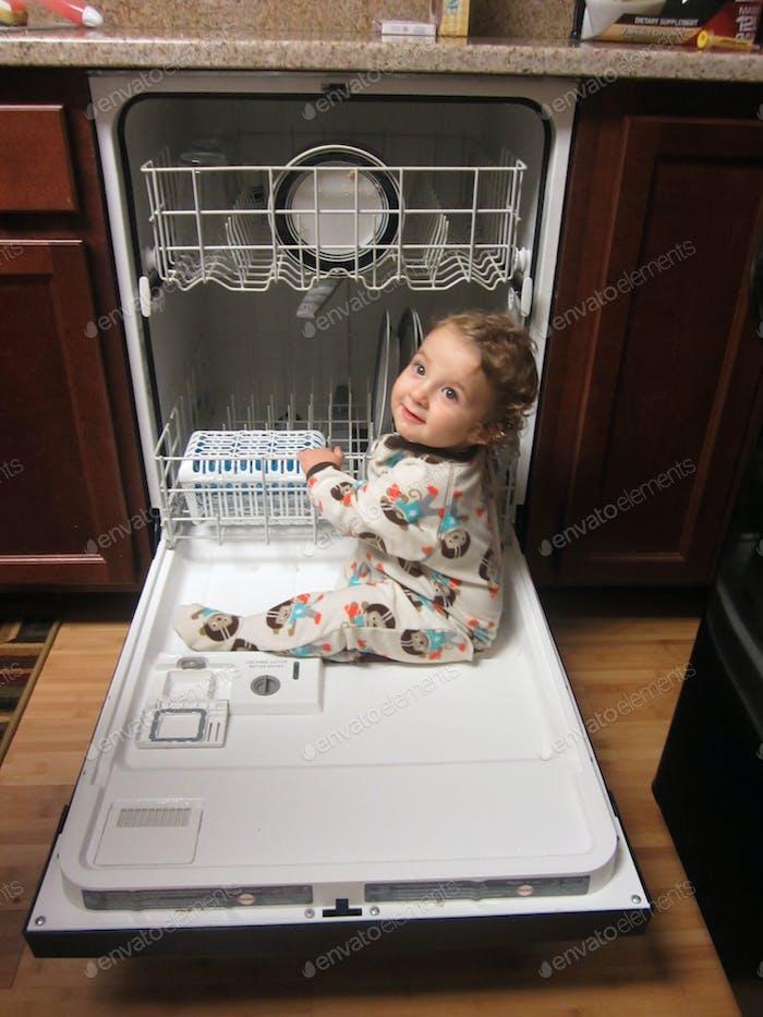 Kleinkind klettert auf der Spülmaschine