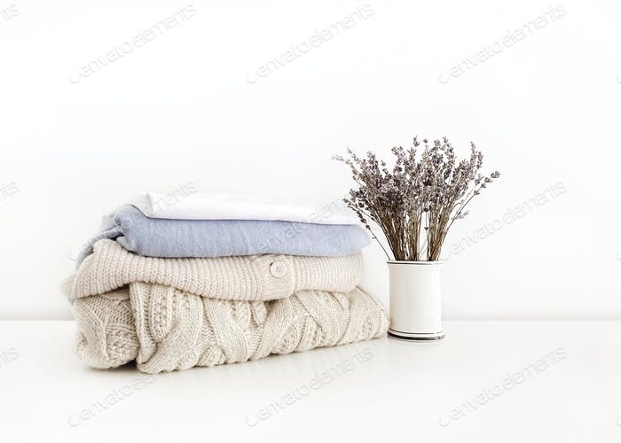 Stack of neatly folded clothes on white background with lavender