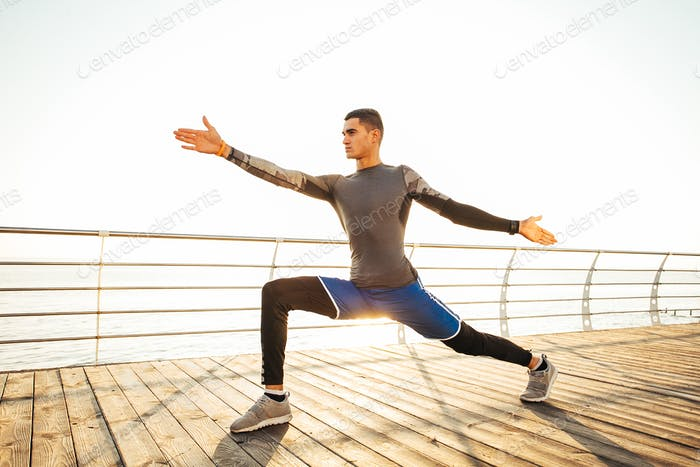 Yogi man practicing yoga exercises at sunrise