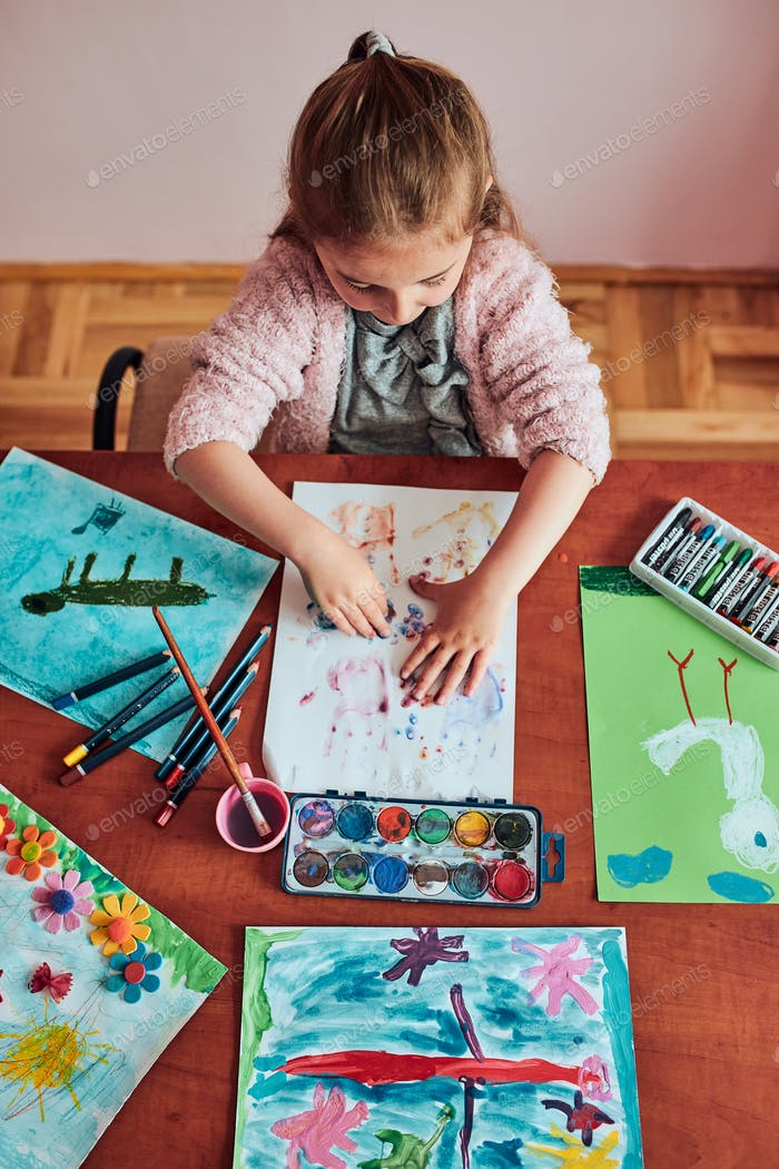 Little girl preschooler painting a picture using colorful paints and crayons