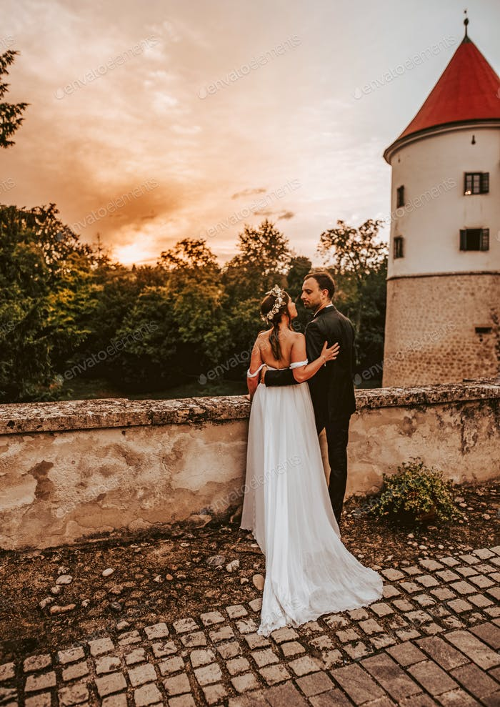 Young newlyweds watching the sunset, standing on a stone bridge
