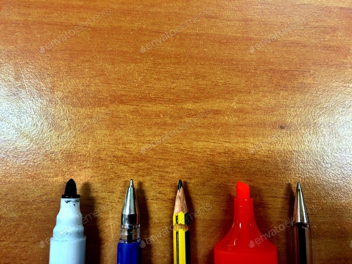 Different kinds of pen on a fine wood table background